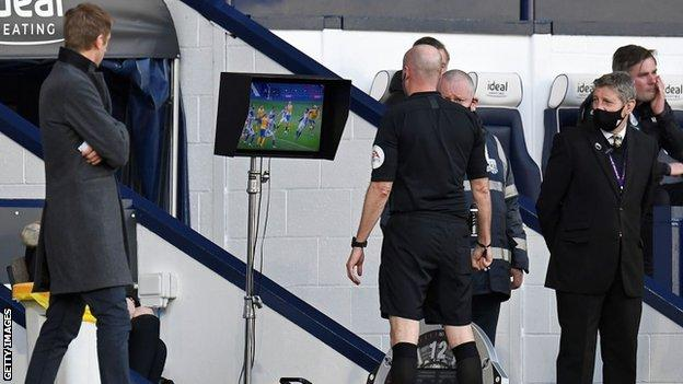 Referee Lee Mason goes to check the pitchside monitor