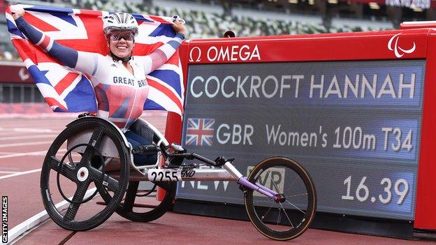 Hannah Cockroft holds up a British flag beside a screen showing her world record time