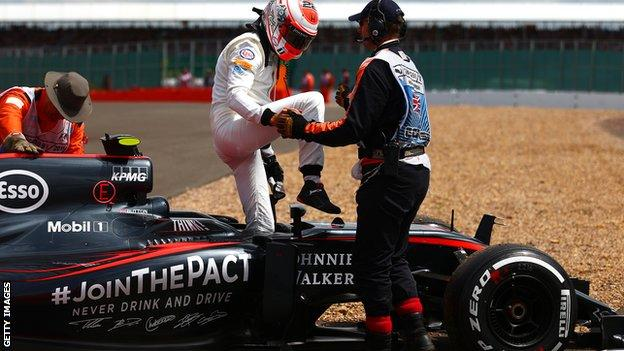 Jenson Button of Great Britain and McLaren Honda climbs out of his car after retiring in the Formula One Grand Prix of Great Britain at Silverstone Circuit on July 5, 2015
