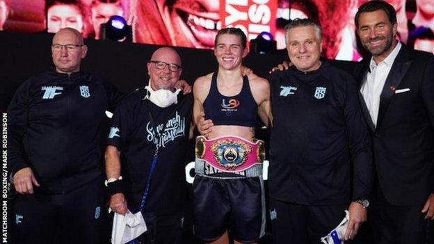 Savannah Marshall celebrates her title win with coach Peter Fury and her backroom team