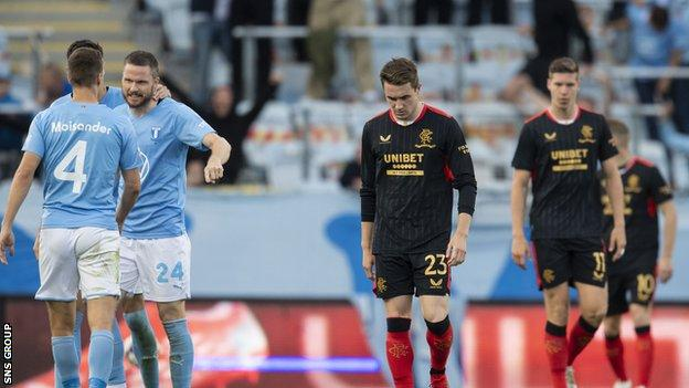Malmo celebrate increasing their lead as Rangers' Scott Wright and Cedric Itten trudge back to halway