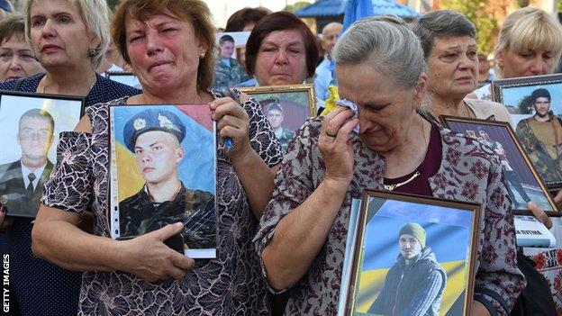 Ukrainian mothers and widows cry as they hold pictures during a memorial rally