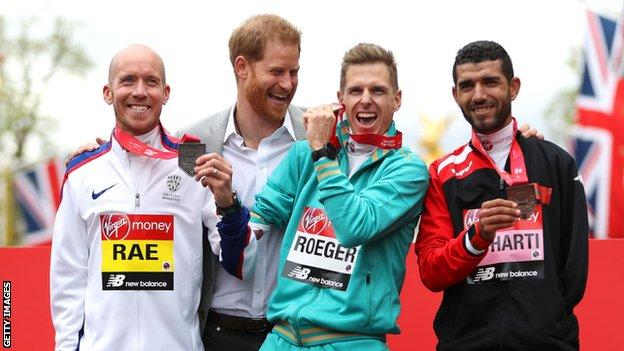 Derek Rae on the London Marathon podium with Australia's Michael Roeger and Morocco's El Harti, joined by the Duke of Sussex