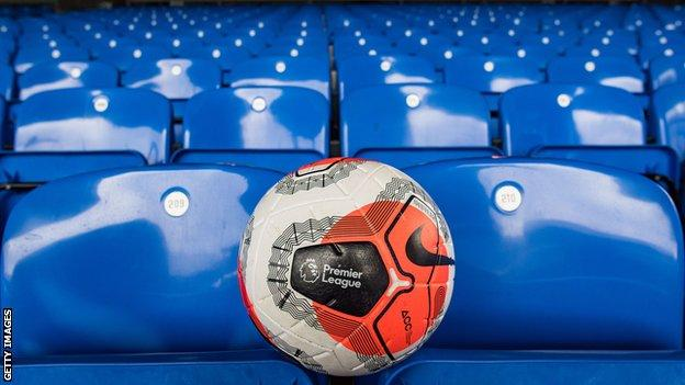 A Premier League match ball rests on a row of empty seats in a stand at a Premier League stadium
