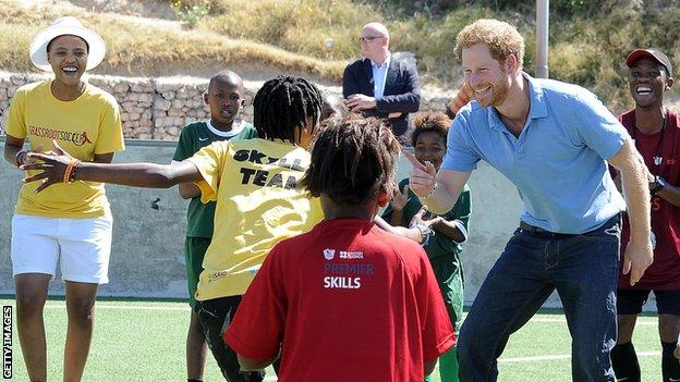Prince Harry plays with a group of children at the Khayelitsha Football for Hope Centre in 2015