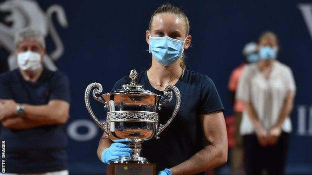 France's Fiona Ferro collects the Palermo Open trophy while wearing a surgical mask and gloves