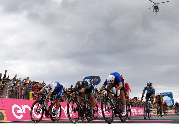 Riders finish stage four of the Giro d'Italia and the helicopter can be seen in the sky above