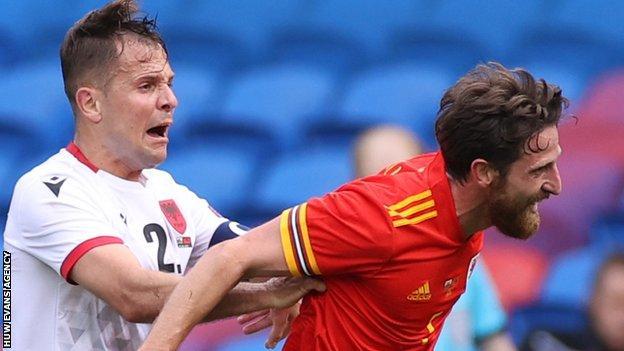 Joe Allen of Wales is pushed by Amir Abrashi