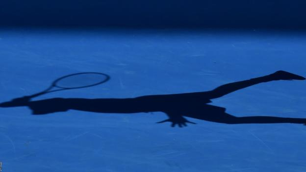 A tennis player casts a shadow