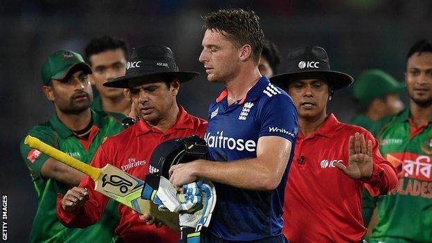 Jos Buttler (centre) walks off after being dismissed against Bangladesh