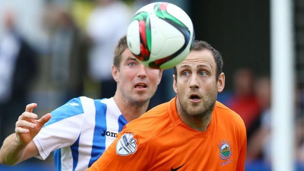 Coleraine defender Steven Douglas competes against Linfield striker Guy Bates during the {Premiership clash at the Showgrounds