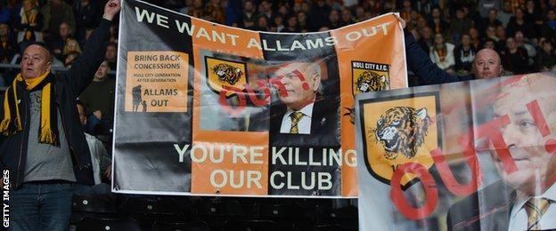 Hull City fans hold banners protesting against Assem Allam. The first banner reads We Want Allams Out, You're Killing Our Club, and Bring Back Concessions. The other has the word Out in front of a picture of Allam