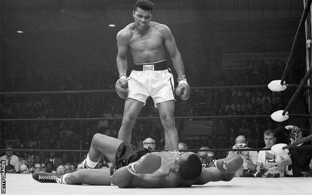 Sonny Liston looks up at a taunting Muhammad Ali