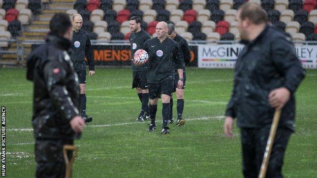 Referee Charles Breakspear inspects the Rodney Parade pitch as ground staff look on