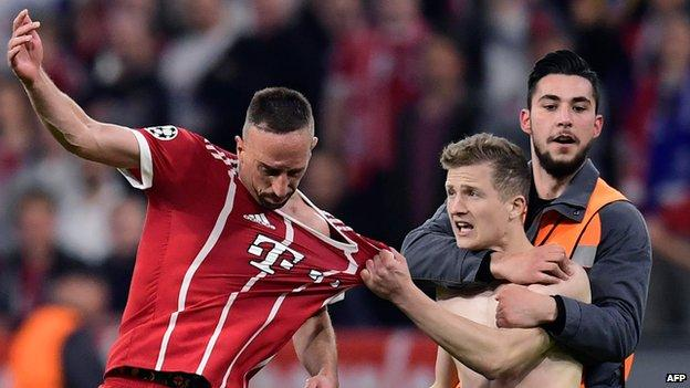 Pitch invader grabs shirt of Frank Ribery