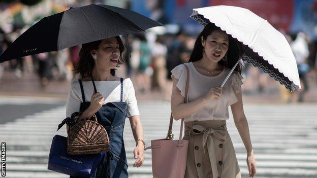 Two women use umbrellas to shield themselves from the sun in Tokyo as temperatures soar in Japan