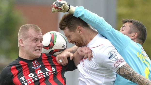 Crusaders striker Jordan Owens contests a high ball with Portadown defender Gary Breen and keeper David Miskelly