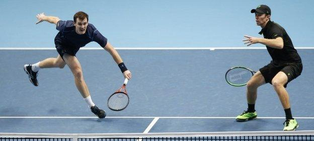 Jamie Murray of Britain, left hits a return watched by his playing partner John Peers of the United States to Bob Bryan and Mike Bryan of the United States during their doubles match