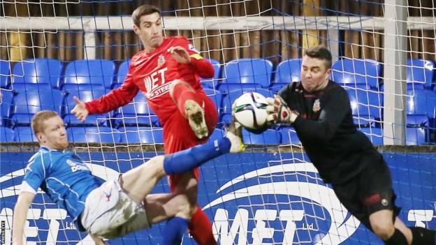 Portadown goalkeeper David Miskelly collects the ball as team-mate Keith O'Hara and Dungannon's David Armstrong look on