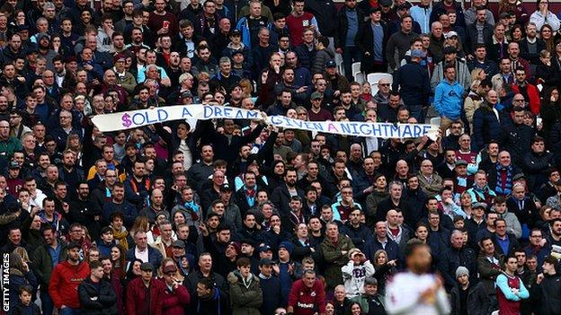 West Ham fans hold a banner protesting against the club's board