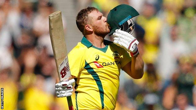 Australia's Aaron Finch kisses the badge on his helmet after reaching a century against England