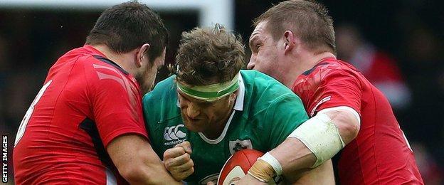 Wales' Aaron Jarvis and Gethin Jenkins tackle Ireland number eight Jamie Heaslip