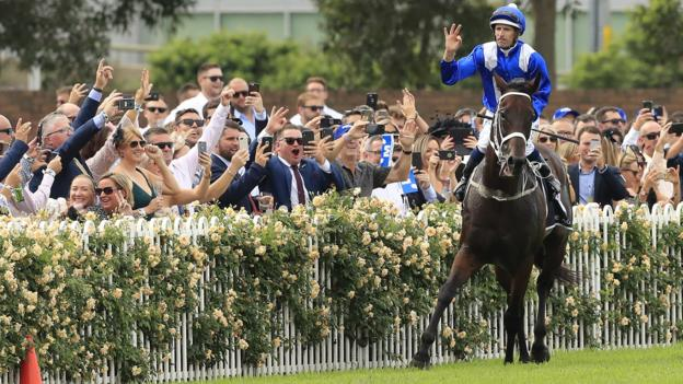 Winx and jockey Hugh Bowman are cheered by fans