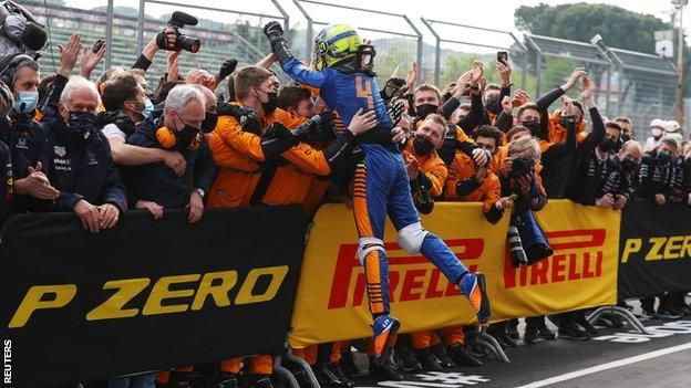 Lando Norris jumps into his team to celebrate after securing third place
