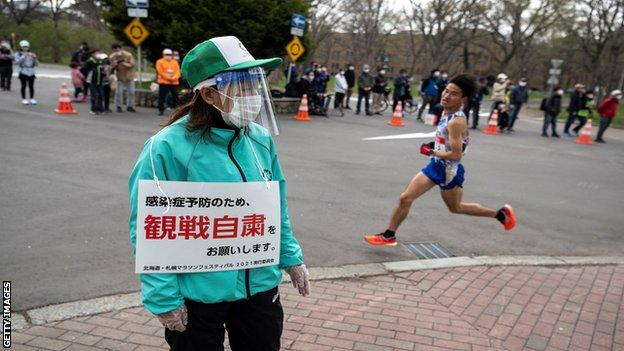 A volunteer (L) holds a placard asking people to refrain from watching the competition to prevent the spread of the Covid-19 coronavirus while an athlete (R) competes in the half-marathon race which doubles as a test event for the 2020 Tokyo Olympics