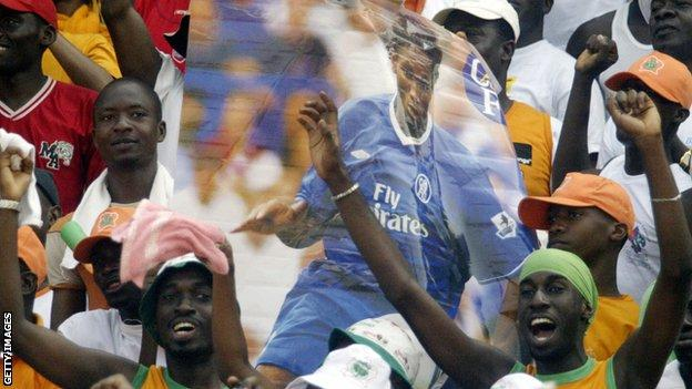 Jubilant Ivory Coast fans hold up a poster of Didier Drogba in Chelsea kit