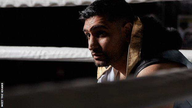 Amir Khan sits in corner of boxing ring.