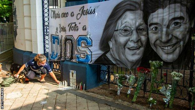 A woman lights a candle at a tribute in La Plata