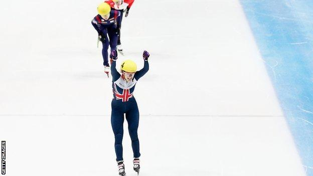 Elise Christie raises her arms aloft after winning the 1000m in Dordrecht