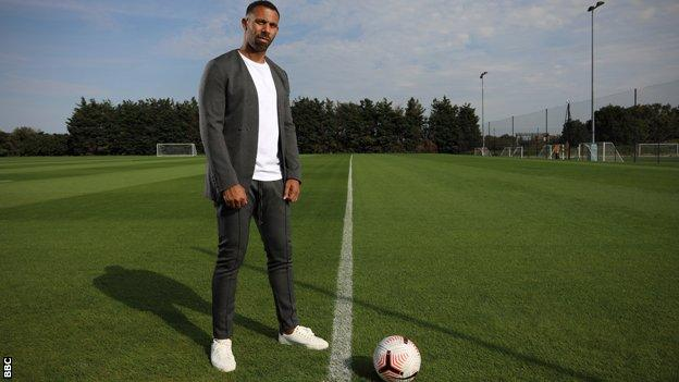 Anton Ferdinand stands on an empty pitch