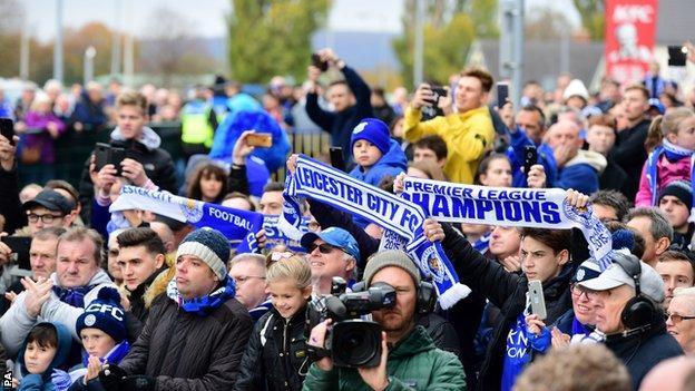 Leicester fans raise flags commemorating their Premier League success in 2015-16
