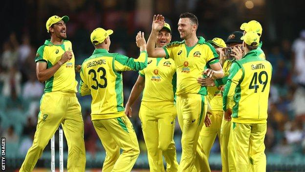 Australia celebrate after fast bowler Josh Hazlewood (centre) takes a wicket against India
