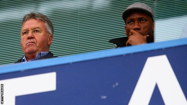 Didier Drogba watches a match with Guus Hiddink