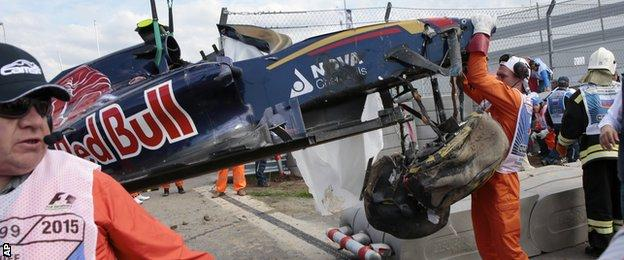 Course marshals remove the crashed car of Toro Rosso driver Carlos Sainz