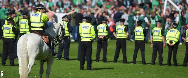 A police cordon helps to get fans off the Hampden pitch