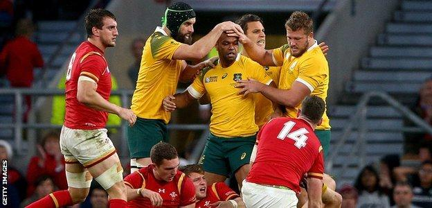 Australia players celebrate after winning a penalty against Wales