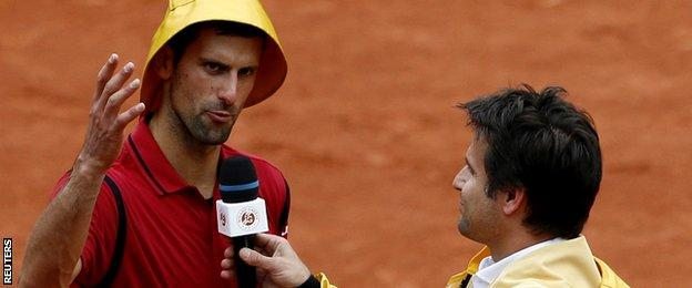 Novak Djokovic wears a rain hat as he answers to former French tennis player Fabrice Santoro