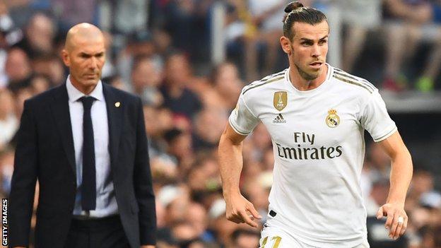 Zinedine Zidane (L) watches Real Madrid's Wales forward Gareth Bale