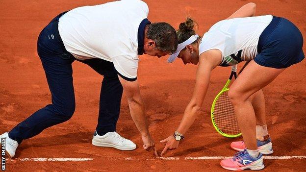 Ο Barbora Krejsikova και ο διαιτητής Pierre Bacchi εξετάζουν τη γραμμή