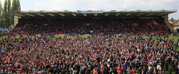 Lincoln City supporters invade the pitch after
