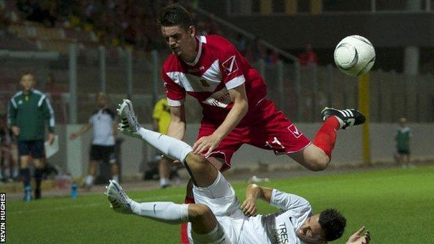 Newtown's Jason Oswell (in red) battles for the ball in Valletta