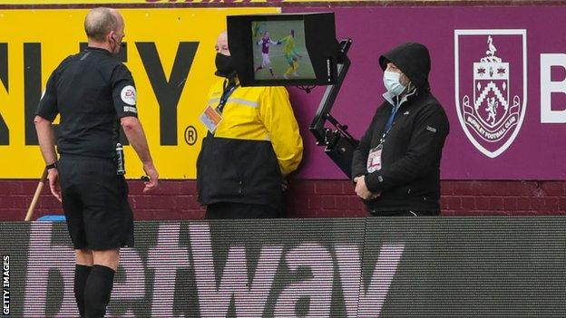 Referee Mike Dean consults VAR