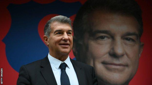 Joan Laporta stands in front of a billboard with his image on it
