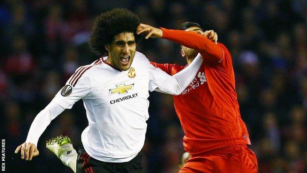 Marouane Fellaini (left) challenges with Emre Can (right)
