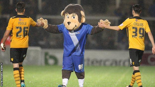 Newport pair Regan Poole and Aaron Collins get a welcome from Hartlepool mascot H'Angus the Monkey during County's recent defeat