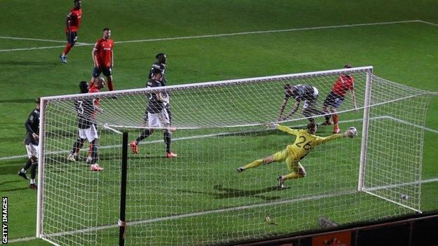 Dean Henderson makes a save against Luton